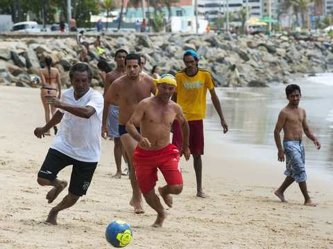 """People play a Sunday """"pelada"""" soccer match on the beach in Fortaleza, a World Cup host city, May 4, 2014."""