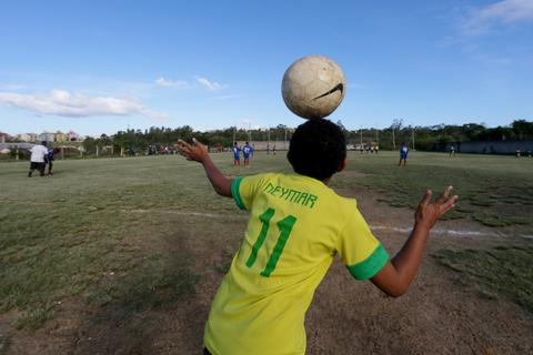 """A boy wears a national soccer team jersey with the name of striker Neymar on it, as he watches a """"pelada"""" soccer match in the Cidade de Deus neighborhood of Port Alegre, a World Cup host city, May 10, 2014."""