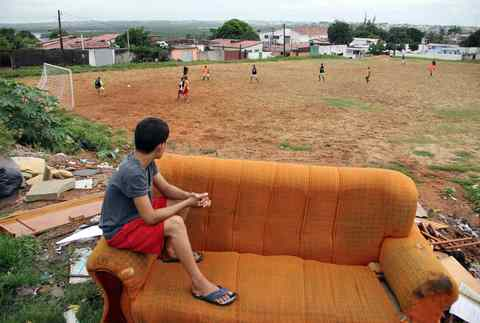 """A boy sits on a discarded couch as he watches a Sunday """"pelada"""" soccer match in the Bom Pastor neighborhood of Natal, a World Cup host city, May 11, 2014."""