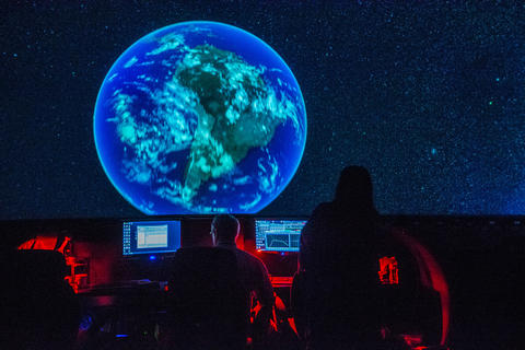 "Mark Webb, center, and producer Christina Delfico watch the end of a production screening of ""Destination Solar System."""