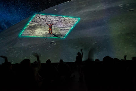 "Spectators wave to astronauts at the future lunar colony during production screening of ""Destination Solar System."""