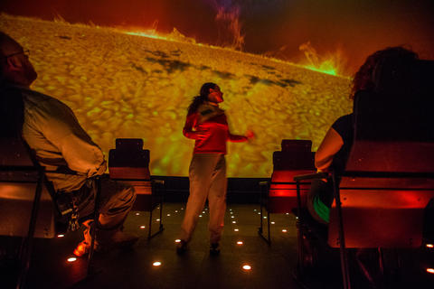 "Becky Poole looks at the sun, as she gives a tour in a production of ""Destination Solar System,"" the new Adler Planetarium show."