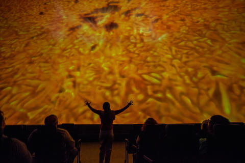 "Becky Poole looks at the sun, as she gives a tour in a production of ""Destination Solar System."""