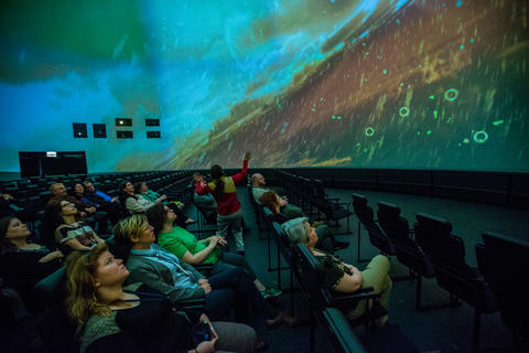 "Spectators look at Titan, the largest moon of Saturn during a production screening of ""Destination Solar System."""