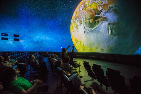 "Spectators look at Io, Galilean moon of the planet Jupiter, during a production screening of ""Destination Solar System."""