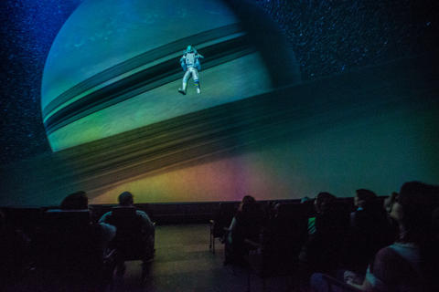 "An image of Jesse, the tour guide, flying over Saturn's rings during a production screening of ""Destination Solar System."""