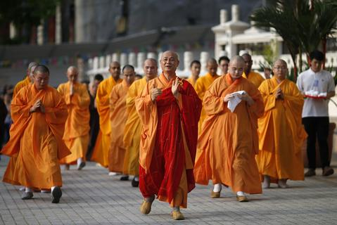 "Buddhist monks perform the ""three steps one bow"" ceremony at Kong Meng San Phor Kark See Monastery on the eve of Vesak Day in Singapore May 12, 2014."