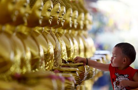 A child drops coins into golden Buddha statues as a symbol of blessings on Vesak Day at the Thai Buddhist Chetawan Temple in Petaling Jaya, near Kuala Lumpur May 13, 2014.