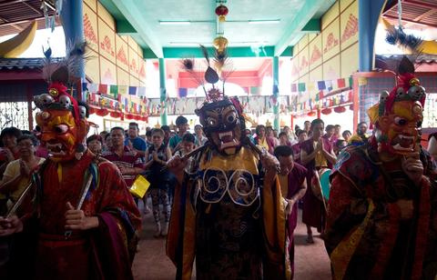 Buddhist priests wearing traditional masks and dress prior to the 'Sunning Buddha ritual' during Wesak day celebrations at a Tibetan Buddhist temple in Ipoh on May 13, 2014.