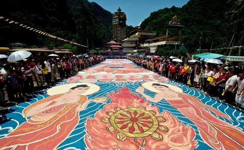 "Buddhist devotees unfurl the 22 year-old, 196 foot-long sacred ""Thangka"" under the sun during Wesak day celebrations at a Tibetan Buddhist temple in Ipoh on May 13, 2014."