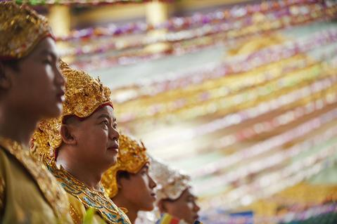 The faithful wear traditional costumes as they take part in a ceremony at Shwedagon pagoda on the full moon day of Kasone Festival to mark Buddha's birthday in Yangon on May 13, 2014.