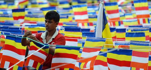 A Sri Lankan man ties Buddhist flags at the roadside in Colombo on May 12, 2014.
