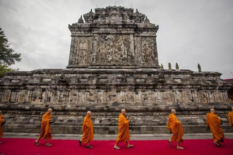 Buddhist monks carry jars of holy water for supplies on Vesak Day, commonly known as 'Buddha's birthday' during holy water ceremony at Mendut Temple on May 13, 2014 in Magelang, Central Java, Indonesia.