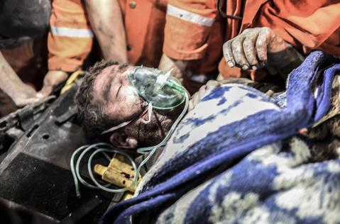 """An injured or death miner is carried by rescuers after an explosion in Manisa on May 13, 2014. Four miner were killed and as many as 300 trapped after a mine collapse in the western Turkish city of Manisa, a local official said. """"At least 200-300 workers were working in the mine when an electric fault caused an explosion,"""" the mayor of Soma, a district of Manisa, told private NTV television."""