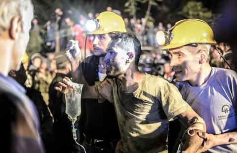 "A miner came out helped by friends after an explosion in Manisa on May 13, 2014. Four miner were killed and as many as 300 trapped after a mine collapse in the western Turkish city of Manisa, a local official said. ""At least 200-300 workers were working in the mine when an electric fault caused an explosion,"" the mayor of Soma, a district of Manisa, told private NTV television."