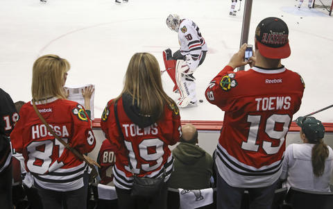 Fans photograph goalie Corey Crawford during warmups.