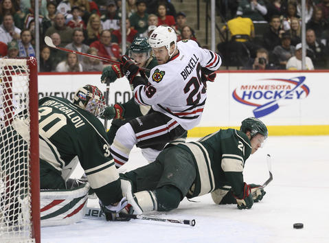 Bryan Bickell eyes the puck as he falls over the Wild's Ryan Suter during the first period.