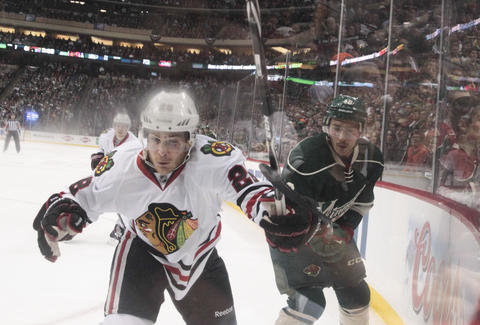 Brandon Saad battles along the boards with the Wild's Jared Spurgeon during the first period.
