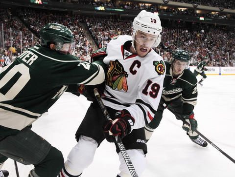 Jonathan Toews battles against the boards with the Wild's Ryan Suter during the first period.