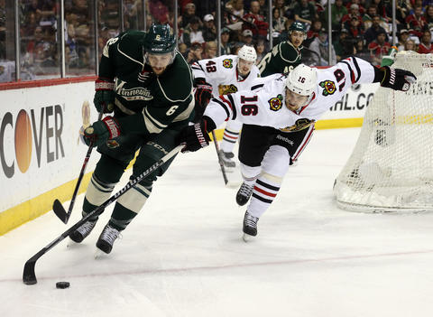 Marcus Kruger tries to get the puck away from the Wild's Marco Scandella during the first period.