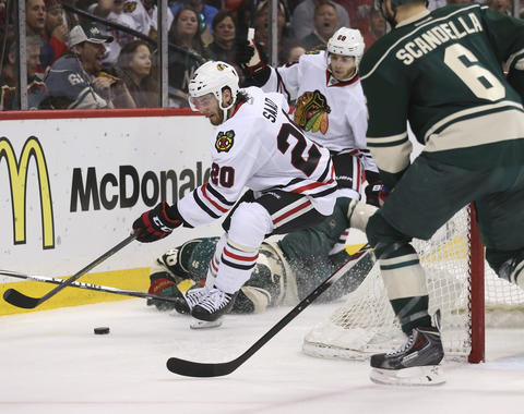 Brandon Saad takes the puck away from the Wild's Jared Spurgeon during the second period.