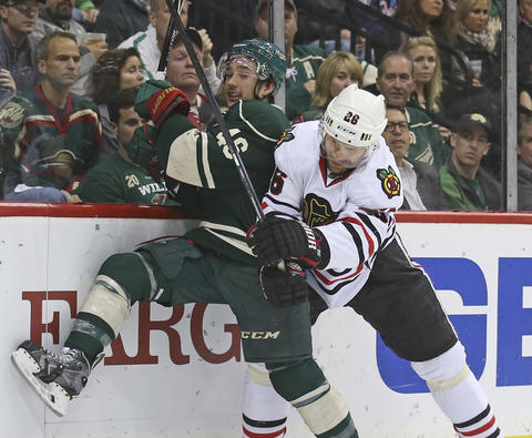 Michal Handzus along the boards with the Wild's Jared Spurgeon during the second period.