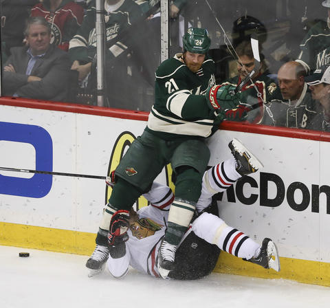 Sheldon Brookbank hits the ice with the help of the Wild's Kyle Brodziak during the third period.