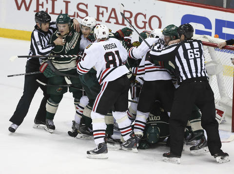 Wild and Blackhawks players mix it up in front of the net of goalie Corey Crawford during the third period.