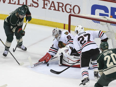 Blackhawks goalie Corey Crawford stops the puck in front of the Wild's Charlie Coyle during the third period.