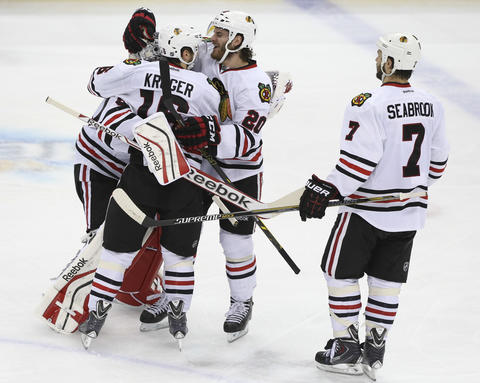 Brandon Saad and Marcus Kruger hug goalie Corey Crawford at the end of their team's 2-1 overtime win.