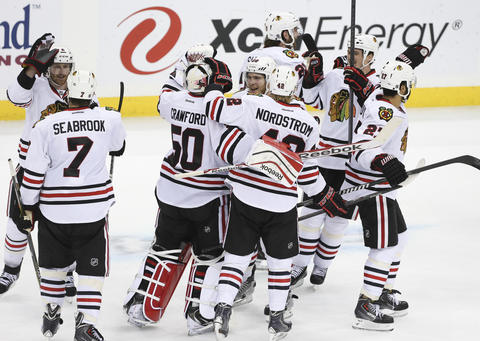 Blackhawks players celebrate their series-clinching win in overtime.