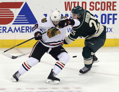 Patrick Sharp and the Wild's Jonas Brodin go for the puck in overtime.