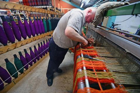 Joh Murdo Macdonald tying in a double width loom at the Harris Tweed Hebrides Company in Shawbost on May 13, 2014 in Stornoway, Scotland.