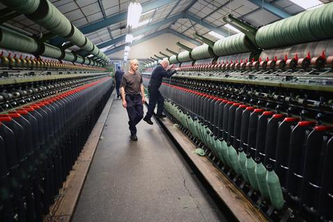 Christopher Morrison works on a spinning frame at the Harris Tweed Hebrides Company in Shawbost on May 13, 2014 in Stornoway, Scotland.