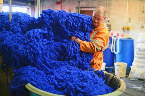 Callum Macleod dying wool at the Harris Tweed Hebrides Company in Shawbost on May 13, 2014 in Stornoway, Scotland.