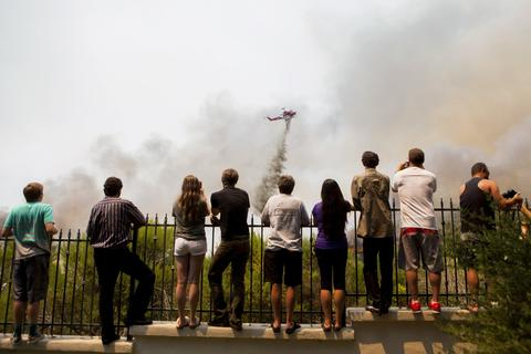 Residents watch firefighters battle the so-called Poinsettia Fire in Carlsbad, California May 14, 2014.