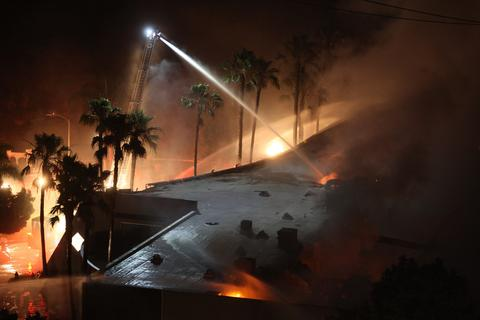 Firefighters spray water on a burning commercial structure at the Poinsettia fire, one of nine wildfires fueled by wind and record temperatures that erupted in San Diego County throughout the day, on May 14, 2014 in Carlsbad, California.