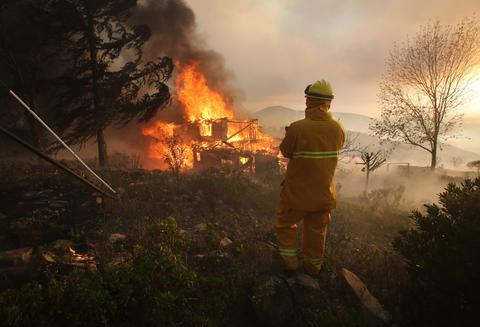 A fireman keeps an eye on a burning house May 14, 2014 in San Marcos, California.
