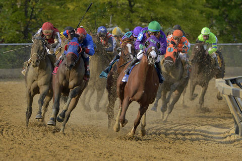 California Chrome, right, breaks out of the fourth turn in the lead during the 139th Preakness at Pimlico Race Course.