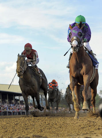 California Chrome, ridden by Victor Espinoza, crosses the finish line to win the 139th Preakness at Pimlico Race Course.