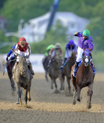 California Chrome, right, ridden by Victor Espinoza, wins the 139th Preakness at Pimlico Race Course.