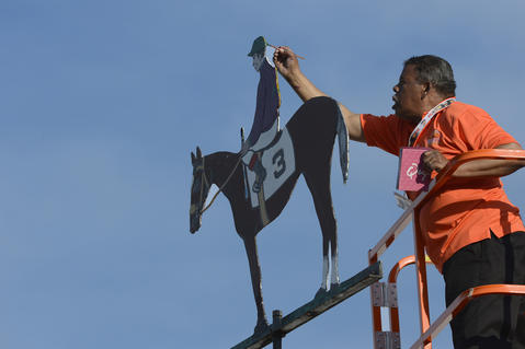 A worker paints California Chrome's colors at Pimlico Race Course.