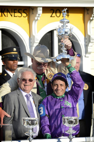 Jockey Victor Espinoza celebrates with co-owner Steve Coburn and trainer Art Sherman after California Chrome wins the 139th Preakness.