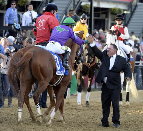 Jockey Victor Espinoza high fives assistant trainer Alan Sherman as he heads to winner's circle after winning Preakness.