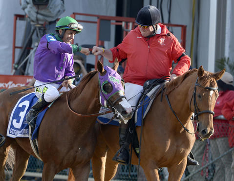Victor Espinoza celebrates the win with the out-rider as California Chrome heads to the winner's circle.
