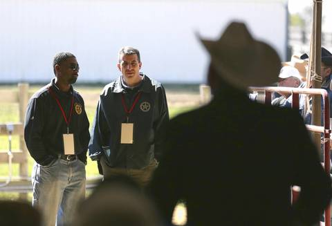U.S. Marshal for the Northern District of Illinois Darryl McPherson, left, and Chief Inspector Jason Wojdylo of the U.S. Marshals Service Asset Forfeiture Division, watch the second day of the federal auction at the Rita Crundwell ranch in Dixon.