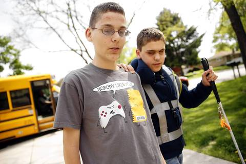 Joseph Williams, right, is helped off the bus by his twin brother Jonathan in front of their home in Countryside.
