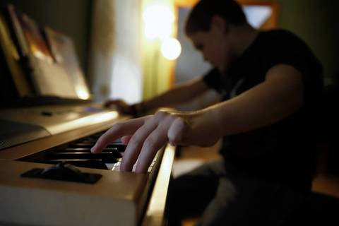 Joseph Williams plays music on his electronic keyboard at home.