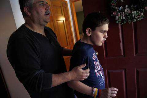 Joe Williams keeps his son Joseph from going outside after a visitor left their home.
