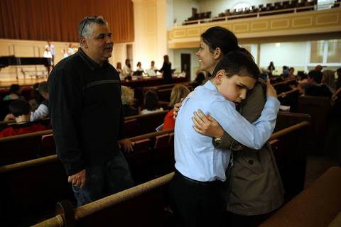 As his father Joe talks to his niece Angie Williams, Joseph Williams hugs her before performing at the Community School of Arts Choirs and Instrumental Concert at Wheaton College.